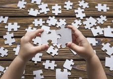 Baby hand collects pieces of the puzzle Royalty Free Stock Photography