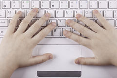 The child's hand on computer keyboard top view closeup Royalty Free Stock Photos