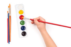 Child's hand dips the brush in watercolor Stock Image