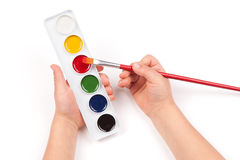 Child's hand dips the brush in watercolor Royalty Free Stock Photography