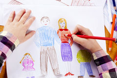 Child's hand drawing. Child's hand with the pencil drawing the нарру family on a white sheet of paper Royalty Free Stock Images