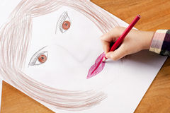 Child's hand drawing. Child's hand with the pencil drawing the moter`s portrait on a white sheet of paper Stock Image