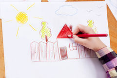 Child`s hand drawing. Child`s hand with the pencil drawing the dream home on a white sheet of paper Royalty Free Stock Photo