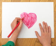 Child's hand drawing red heart. Stock Photography