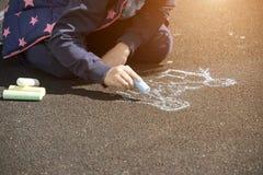 Chalk drawings on asphalt. Child`s hand draws hearts, drawings chalk on asphalt stock photography