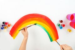 Child`s hand draws a rainbow on a white background. The child`s hand draws a rainbow on a white background Royalty Free Stock Photos