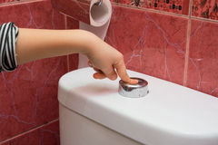 Child`s hand finger presses button on the water draining into the toilet bowl, close-up Royalty Free Stock Photos
