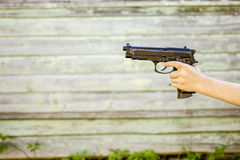 Child's hand with a gun, isolated on old wall background, closeu Royalty Free Stock Image
