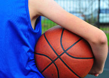 Child`s hand holding the basketball ball Royalty Free Stock Photography