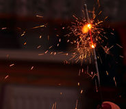 Child's hand, holding a burning sparkler. Light royalty free stock images