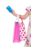 Child`s hand holding credit card and colorful shopping bags. In isolated white background Stock Photo