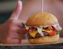 Child's hand holding juicy and yummy hamburger. Child's hand holding juicy and  hamburger Stock Image