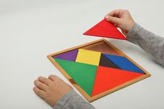 Child`s hand holding a missing piece in a tangram stock images