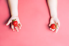 Child`s hand holding strawberry on pink background, plate of strawberries. healthy eating concept. Top view, flat lay Royalty Free Stock Photos