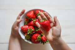 Child& x27;s hand holding strawberry on rustic concrete background. Summer healthy eating concept. Top view stock photography