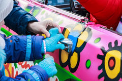 Child`s hand holds doorhandle of pink colorful car Royalty Free Stock Image