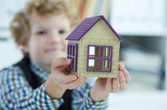 The child`s hand holds the house. Family, purchase of housing, apartment, mortgage, inheritance. The child`s hand holds the house. Family, purchase of housing Stock Photos
