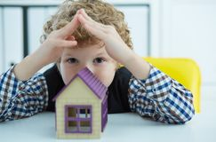 The child`s hand holds the house. Family, purchase of housing, apartment, mortgage, inheritance. The child`s hand holds the house. Family, purchase of housing Royalty Free Stock Photos