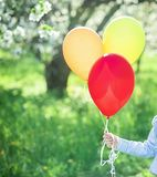 the child& x27;s hand holds three air balloons stock photography