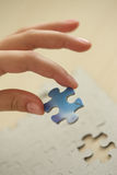 Child's hand, inserting missing piece of puzzle. Final Piece. Child's hand, inserting missing piece of blank puzzle into the hole royalty free stock photo
