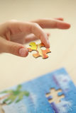 Child's hand, inserting missing piece of puzzle. Final Piece. Child's hand, inserting missing piece of blank puzzle into the hole royalty free stock photography