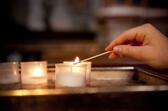 Child's hand lighting a candle in church. Young girl in church lighting a candle with a match Royalty Free Stock Image