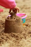 A child`s hand making a sand castle in the sandbox, sand therapy through playing. Close up of a child`s hand making a sand castle in the sandbox, sand therapy Royalty Free Stock Photos