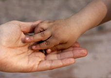 Child`s hand on mother`s hand. On brawn background Royalty Free Stock Photos