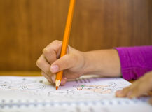 Child`s hand with orange pensil drawing in album Royalty Free Stock Photo