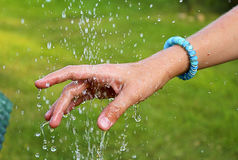 A child`s hand over a fountain. With water splashing Stock Images