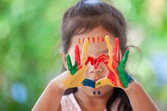 Child`s hand with painted colorful watercolor make heart shape. On green nature background stock photos