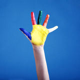 Child's hand painted with multicolored finger paints on blue. Background stock photos