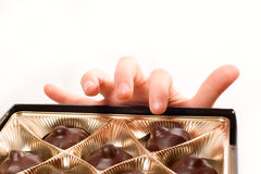 Child's hand picking chocolate candy from box isol Stock Photos