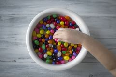 A child`s hand picking up candy from a white plate stock image