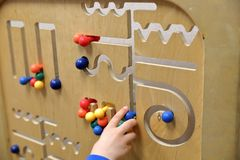 Child`s hand plays with wooden puzzle stock photo