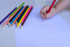 The child`s hand preparing to write on a white sheet of paper with colored pencils.  Education and children activities concept stock photos