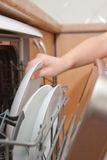 Child's hand put plate in dishwasher Stock Image