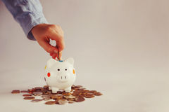 Child`s hand put into white piggybank money coins. Stock Images