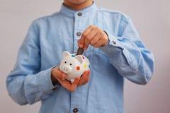 Child`s hand put into white piggybank money coins. Royalty Free Stock Image