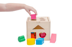 Child's hand putting wooden toy shape into wood box Royalty Free Stock Photos