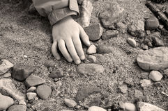 Child's Hand on Sand and Stones Royalty Free Stock Photos