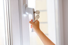 Child's hand on secure window handle Stock Image