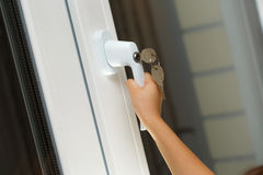 Child's hand on secure window handle Stock Photo