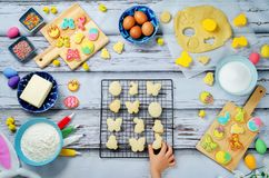 Child`s hand with Sugar Easter cookies and ingredients for bakin royalty free stock photos