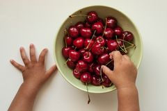 Child`s hand taken a cherry from a plate. stock images