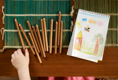 Child's hand takes the pencil on  table to draw Stock Images