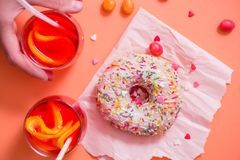 Child's hand takes sweet pastryFrosted sprinkled donut on pink background. Tubules for a cocktail. Spilled orange candy. Cold dri royalty free stock photos
