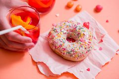 Child's hand takes sweet pastryFrosted sprinkled donut on pink background. Tubules for a cocktail. Spilled orange candy. Cold dri royalty free stock photography