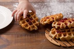 Child`s hand takes Tasty homemade waffle and strawberry jam stock photography