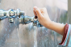Child's hand with tap water Royalty Free Stock Image